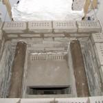 De naverbrandingskamer links en rechts van het donkere gedeelte gaat het hete rookgas omlaag langs de opening en geeft de warmte af aan de stenen